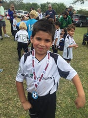 This file photo shows a young player after his team won its division of the Optimist Club soccer league. The Optimist Club of Naples, which hosts more than 1,800 children in its youth sports program, had to cancel its soccer season one week into the year because of the coronavirus.