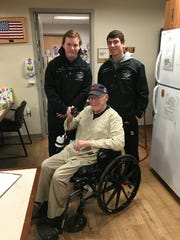 Army veteran Jack Smith is visited by Plymouth hockey players Jack Back and Colton Borke at the VA Hospital in Ann Arbor.