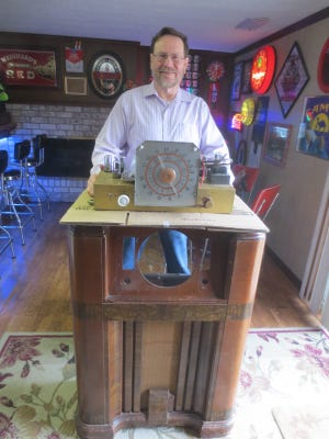 Ken Iman stands behind a 1942 Crosley radio cabinet with a round, Art Deco dial he is restoring.  The radio is one of more than three dozen he has in his home as part of his collection or as restoration projects.