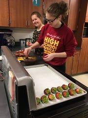 Shianne Lindsay (left) and Claudia Adamson dip strawberries