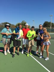 Mike Hill (in fluorescent shirt, shoes) has helped Gabrielle Magnant, far right, collect tennis cans for Ronald McDonald House