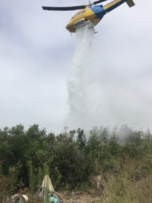 A Ventura County helicopter makes a water drop on a brush fire near Emma Wood State Beach campground Saturday in Ventura.