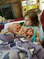 Brielle Reznik (right) is comforted by her sister Arielle.