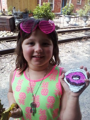 "Anna Glatfelter, 6, of Glen Rock, poses with a painted rock she found along the York County Heritage Rail Trail in New Freedom. The rock is part of a new ""kindness rock"" trend in which people paint colorful pictures and inspirational sayings on rocks and leave them for others to find."