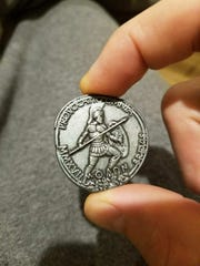 Doug Freeman shows the Spartan coin he received for