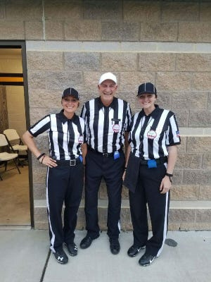 Stefanie Jones, left, and Amy Joostberns, far right, pose for a photo with their father Tony Joostberns prior to working a varsity football game. Jones and Amy Joostberns are among 14  registered female high school football officials in the state.
