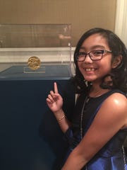 Katherine Alayon stands with the Congressional Gold Medal awarded to her grandfather and the many other Filipino veterans of World War II.