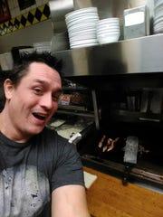 Bowen takes a selfie as his bacon cooks.