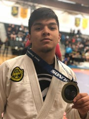 Aidan Borja celebrates his gold medal in the mens gi, blue belt medium heavy division at The Proving Grounds Submission Only BJJ Tournament held at Green River Community College in Auburn, Wash.