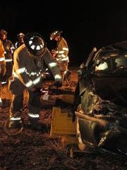 "Afton firefighters use the ""Jaws of Life"" to cut into"