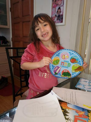Chabad of Rock Hill has taken their Hebrew School online with resources from Chabad Hebrew School International. Students received a packet filled with Passover crafts and material to continue learning the Hebrew Aleph-Bet. Above, Sabrina Pine shows off her seder plate  that she made for the upcoming Passover seder. Other children can visit ckids.com/hslive each Wednesday until Hebrew school can reopen its doors.