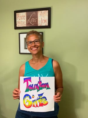 Taunton resident Gina (Paulo) Galarza holds up a sign that she designed in her home.
