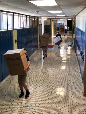Aquin High School students carry boxes containing air purifier machines into the school before the first day of classes. Donors sent in funds to pay for the machines and now every classroom in the elementary and high school has one to help battle the coronavirus.