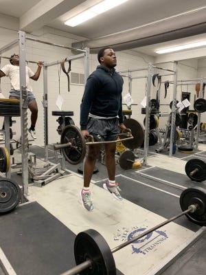 An Effingham County athlete lifts in the school weight room during voluntary conditioning workouts. Starting Monday of this week, schools could use balls and other sports-related equipment in groups of 50 during workouts.