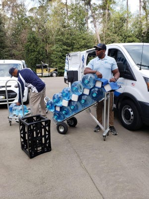 """Divine Health Water 4U employees Alfred Williams (left) and Joshua Jackson deliver 250 gallons of bottled """"alkaline water"""" to the Augusta National Golf Club before the start of the Masters Tournament."""