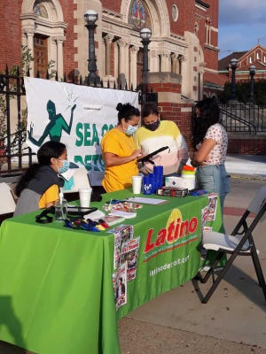 In front of Holy Redeemer Church in southwest Detroit, Claudia Rivera of Latino Press informs people how to fill out the Census2020 form.