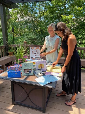 Julia Hanna, left, and Kat DePizzo stamp books with the Harper's Corner seal as they experiment with display ideas. Hanna founded the nonprofit organization with the mission of donating books about diversity to central Ohio elementary schools.