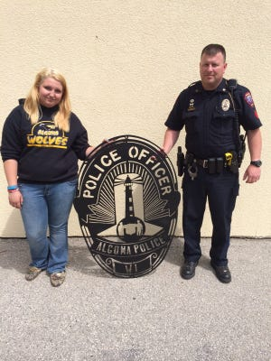Sgt. Ryan Roesch and Savanna Brunette, one of the students who designed and made the new sign for APD, which is fashioned after the police badges worn by officers.