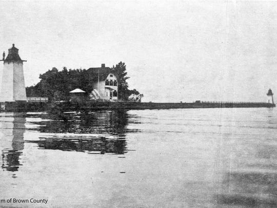 This early 20th century photograph shows the Grassy Island Lighthouse that was a part of the Grassy Island Range Lights. The lighthouse was built to guide water traffic through the channel into the port of Green Bay. In 1866, funds were appropriated for dredging of the channel and construction of the lighthouses. One hundred years later, the two towers were moved to the Green Bay Yacht Club.