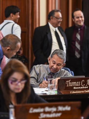 Sen. Tom Ada, seated center, discusses details of a