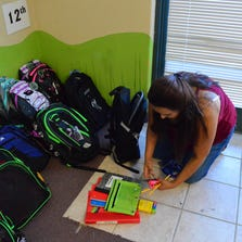 Roberta Franco, director of The Salvation Army, pulls items out of a backpack set aside to give to an eligible student.