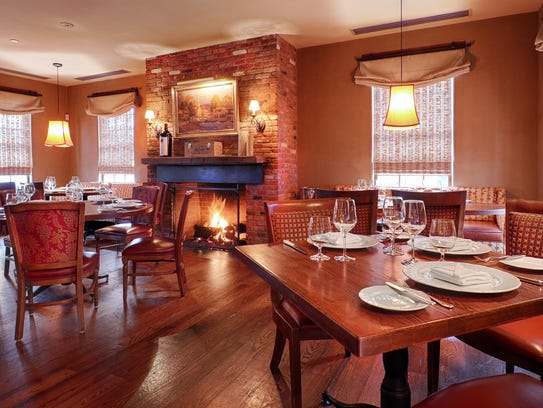 One of two fireplaces within the two-story main dining