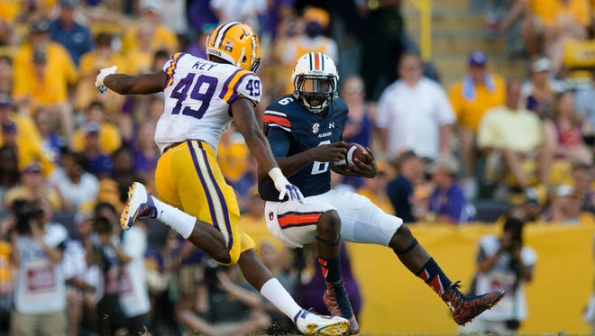 Auburn Tigers quarterback Jeremy Johnson (6) runs downfield as Louisiana State defensive end Arden Key  attempts to tackle him during the NCAA football game between LSU Tigers and Auburn on Saturday, Sept. 19, 2015, at Tiger Stadium in Baton Rouge, La. LSU Tigers defeated Auburn Tigers 45-21.
