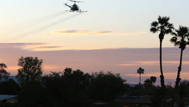 The Coachella Valley Mosquito and Vector Control District sprays larval mosquito treatments by helicopter in Indio on Saturday, March 11, 2017.