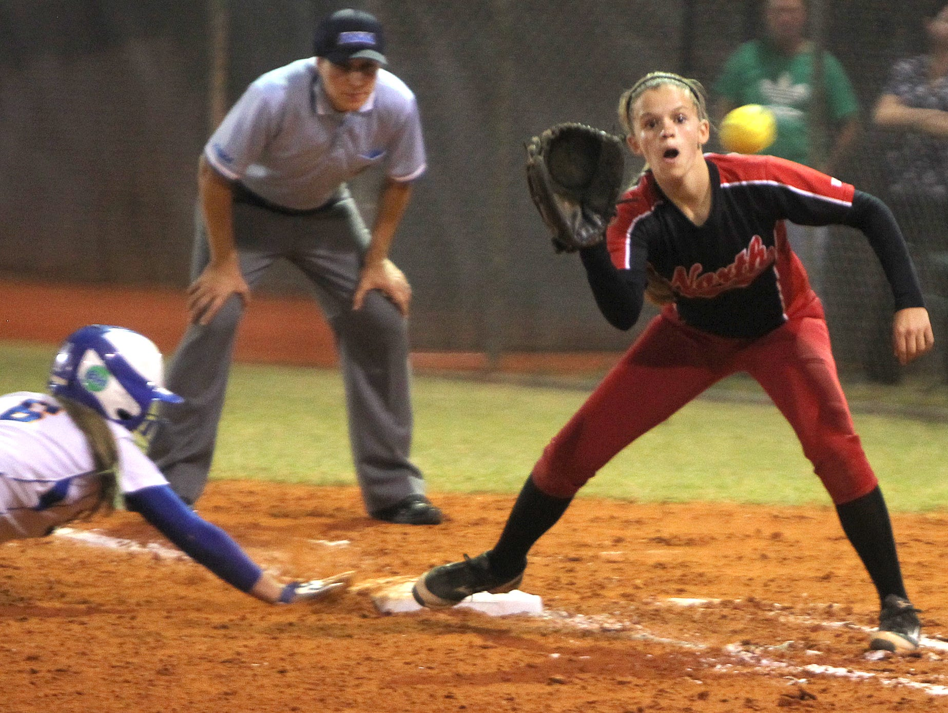 Auburndale's Sylvia Welsh dives back to first as North's Emma Johnson eyes the ball at the 6A-3 softball final Friday.