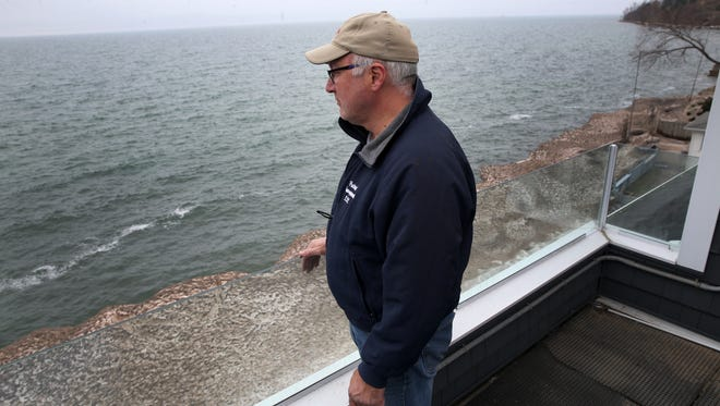 Phil Miglioratti looks out over Lake Ontario from his third floor porch. Miglioratti built a breakwall out of riprap, an  array of lager boulders that successfully protected his property during the recent storms. The break wall is currently still locked in a block of ice from the storms.