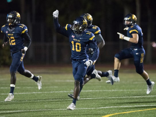 D'Andre St. Jean (10) and other Naples defenders celebrate coming up with a fumble during the game against Port Charlotte at Naples High on Nov. 10.