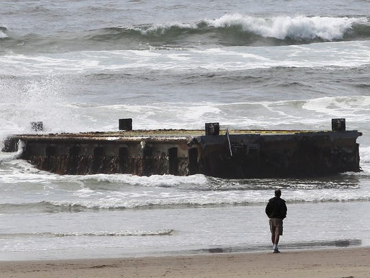 In this 2012 photo, a man looks at the tsunami dock that washed ashore on Agate Beach in Newport.