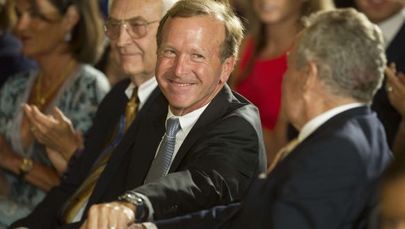 Chairman of Points of Light Neil Bush shakes hands