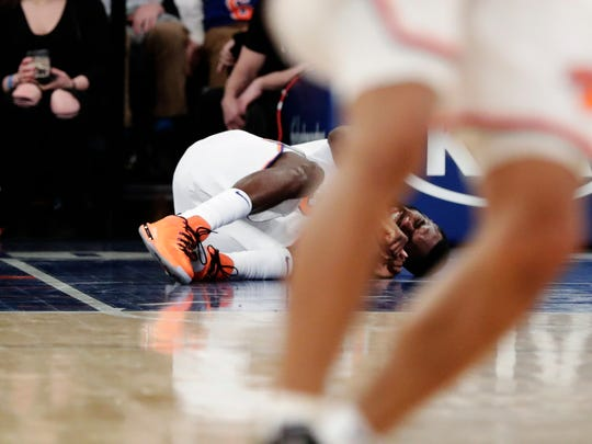 New York Knicks' Tim Hardaway Jr. lies on his side after an injury during the second half of the team's NBA basketball game against the Miami Heat on Friday, April 6, 2018, in New York. The Knicks won 122-98.