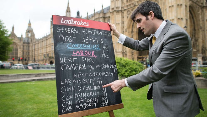A bookmaker displays the latest odds on the result of the upcoming United Kingdom general election outside the Houses of Parliament in central London on May 6, 2015. Britain's political leaders campaigned for the most unpredictable election in living memory which could yield no clear winner and weeks of haggling over the next government.