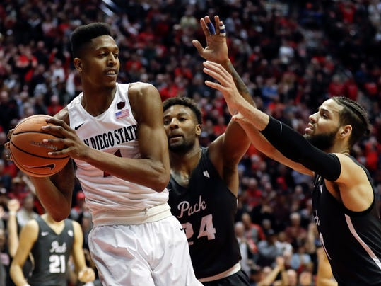 San Diego State forward Malik Pope (21) looks to pass as Nevada guard Jordan Caroline (24) and forward Cody Martin (11), right, defend during the second half of an NCAA college basketball game Saturday, March 3, 2018, in San Diego. (AP Photo/Gregory Bull)