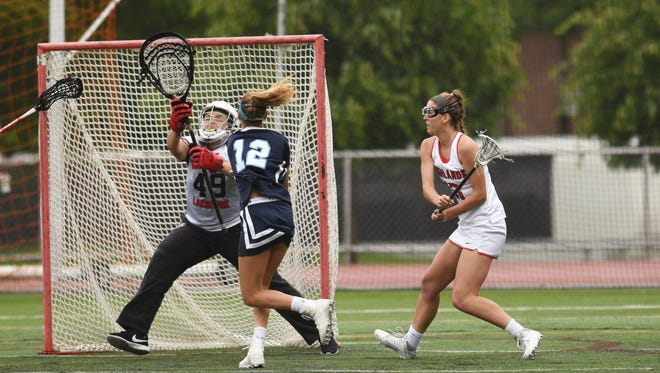 IHA's Emma Zabransky (12) attempts a shot against Northern Highlands goalie Victoria Marino in the North 1, Group 3 final on May 25. Looking on is Northern Highlands's Grace Travers.