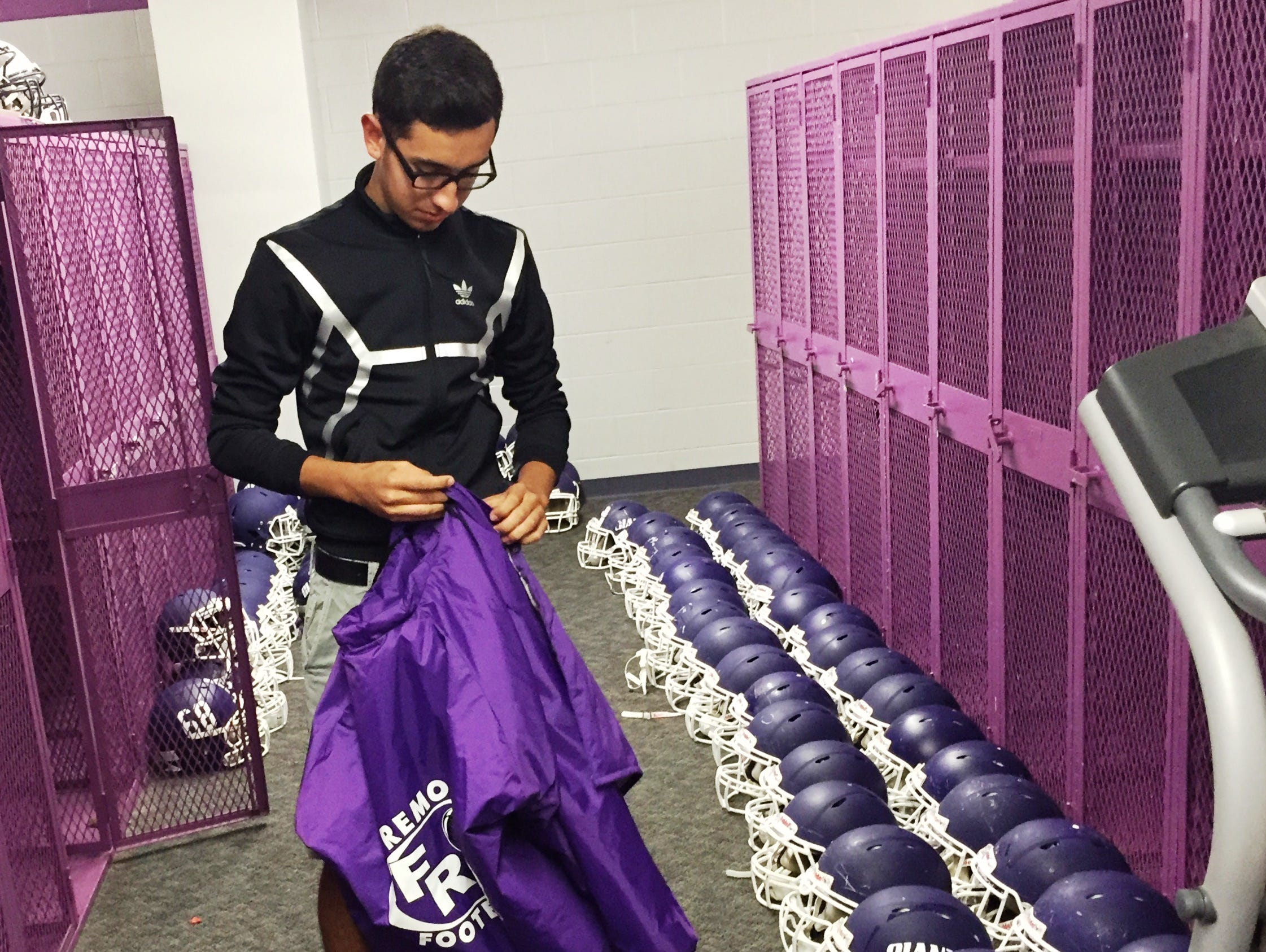 Fremont Ross sophomore Mikey Contreras zips up a jacket before turning it in during the team's equipment return on Monday.