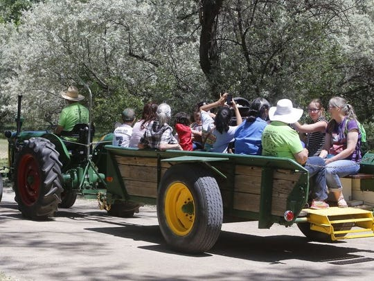 A group of Riverfest visitors enjoys a tractor ride through Animas Park during last year's event.