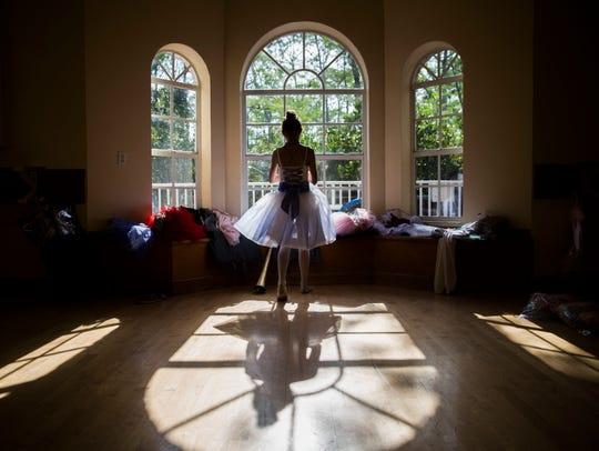 Alexandra Uscatu, 11, runs to do a costume change during