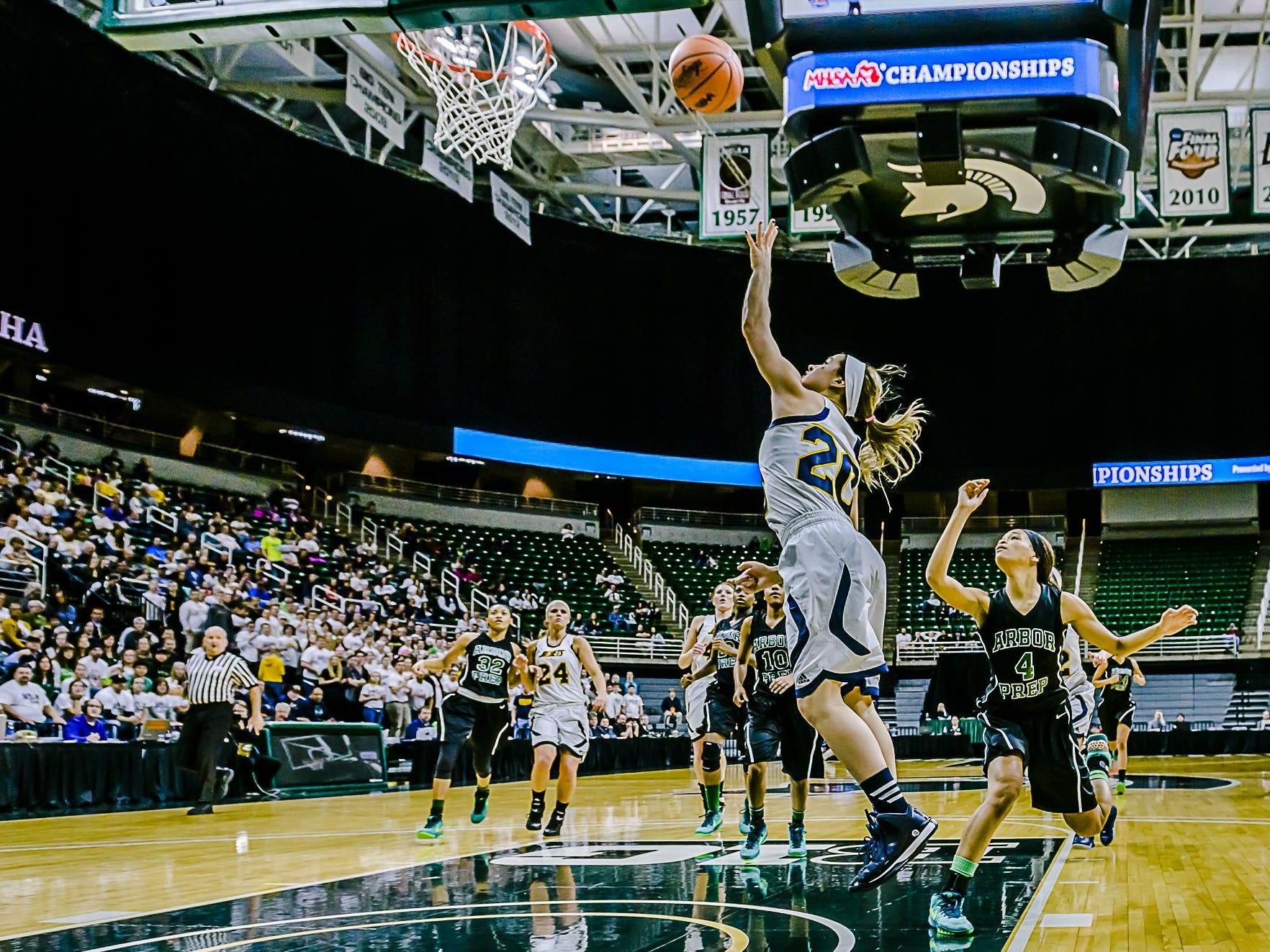 Brooklyn Dolloff ,20, of Ithaca lays the ball in over Nastassja Chambers ,4, of Ypsilanti Arbor Prep during 1st quarter action in their Class C state semifinal game Thursday March 17, 2016 at the Breslin Center in East Lansing. KEVIN W. FOWLER PHOTO