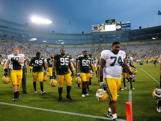 Green Bay Packers players leave the field after a weather delay during Packers Family Night at Lambeau Field in 2011.