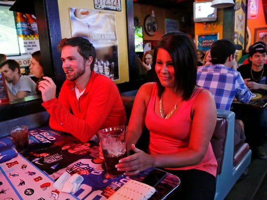 Tyler Lowe and Jodi Kaufman enjoy drinks with friends Thursday, April 9, 2015, at Jake's Roadhouse in West Lafayette. Kaufman said he has used Uber to avoid driving while enjoying nights out at the bars.