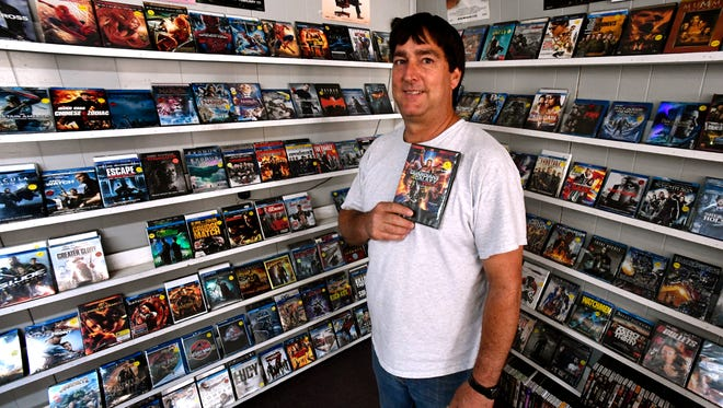 """Jay Ward holds a copy of his most-recent favorite movie, """"Guardians of the Galaxy, Vol. 2,"""" on Thursday. Ward is the owner of Video Mania in Anson, which is closing after 31 years."""