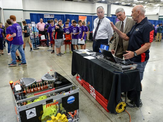 Rusty Burns, left, Anderson County Administrator, Burriss Nelson, middle, Economic Development Manger/Director, listen to Jerry Wayman at the Borg Warner booth while eighth grade students from R.C. Edwards Middle School look at other booths during the Anderson Oconee Pickens County Schools Business Showcase at the Civic Center of Anderson on Tuesday.