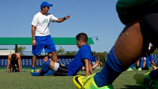 Coach Bob Butehorn speaks to FGCU men's soccer players during practice on Aug. 27, 2014.