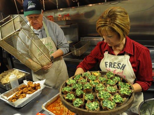 Karen Moore and John Schreiber prepare food at Benton party venue Sainte Terre Sunday.