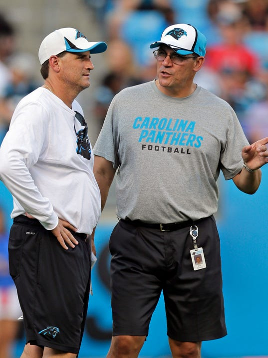 Carolina Panthers head coach Ron Rivera, right, talks with offensive coordinator Mike Shula, left, during an NFL football practice at the team's Fan Fest in Charlotte, N.C., Friday, July 25, 2014. (AP Photo)