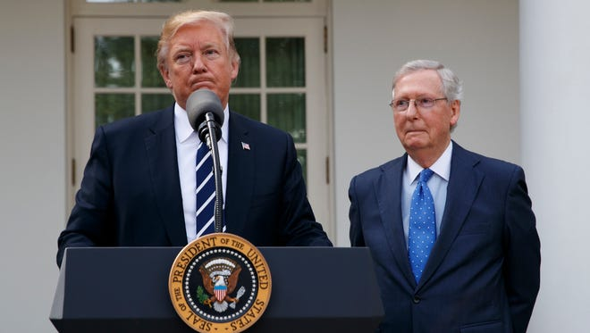 Senate Majority Leader Mitch McConnell, R-Ky., listens as President Trump speaks with reporters in the Rose Garden on Oct. 16, 2017.