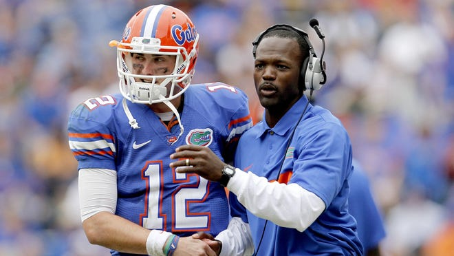 Florida quarterback John Brantley talks with wide receivers coach Aubrey Hill during the Nov. 19, 2011 game against Furman at Ben Hill Griffin Stadium.